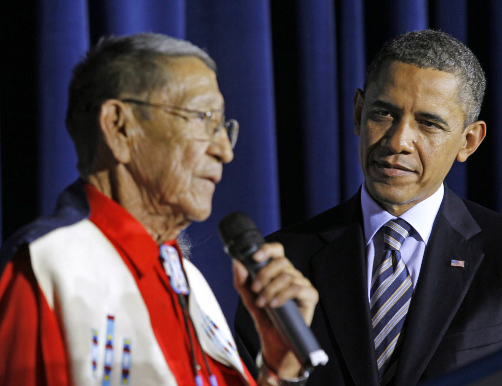 "President Barack Obama listens as Hartford ""Sonny"" Black Eagle delivers remarks at the White House Tribal Nations Conference at the Interior Department in Washington. Native American tribal leaders are concerned that steady progress on their issues might be undermined if President Barack Obama and Congress make deep spending cuts in order to avoid the ""fiscal cliff."" More than 500 tribal leaders were taking those concerns to the fourth White House Tribal Nations summit, which convenes Wednesday, Dec. 5, 2012. Obama is scheduled to address the group in the afternoon."