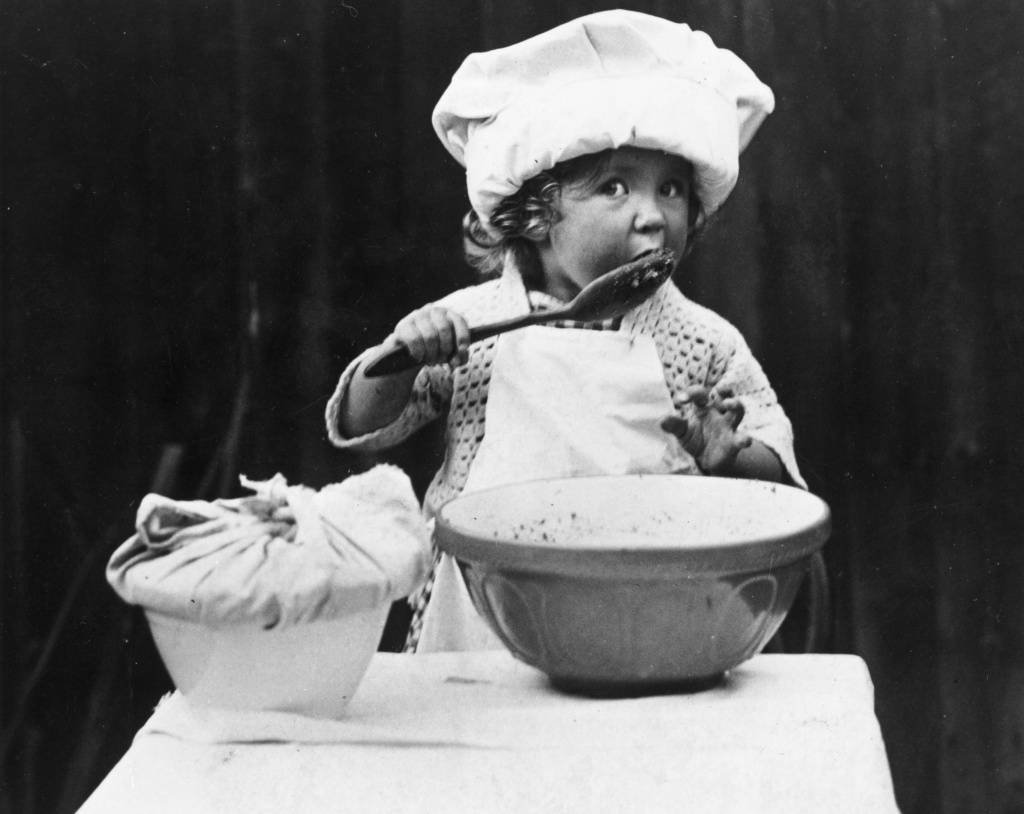 A little girl licking a spoon after stirring the cake mixture in 1935.
