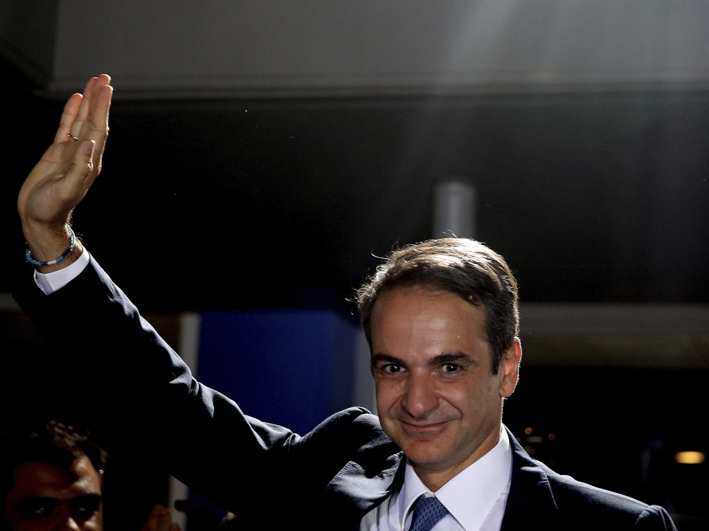 Greek opposition New Democracy conservative party leader Kyriakos Mitsotakis waves to his supporters after a win in parliamentary elections at the New Democracy headquarters in Athens on Sunday.