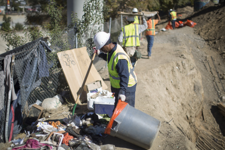 Cal Trans workers clean trash at a bridge construction site near the concreted channel of the Arroyo Secco Creek
