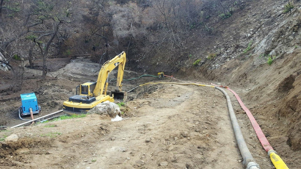 Crews with the Los Angeles Bureau of Engineering  pump water out of the landslide on the south side of La Tuna Canyon Road on Sunday, March 25, 2018. The road reopened later that night.