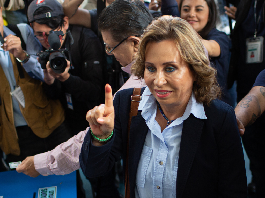 Sandra Torres, former first lady and presidential candidate for the National Unity of Hope (Union Nacional de la Esperanza) party, center, displays an inked finger after voting during presidential elections in Guatemala City, Guatemala, on Sunday.