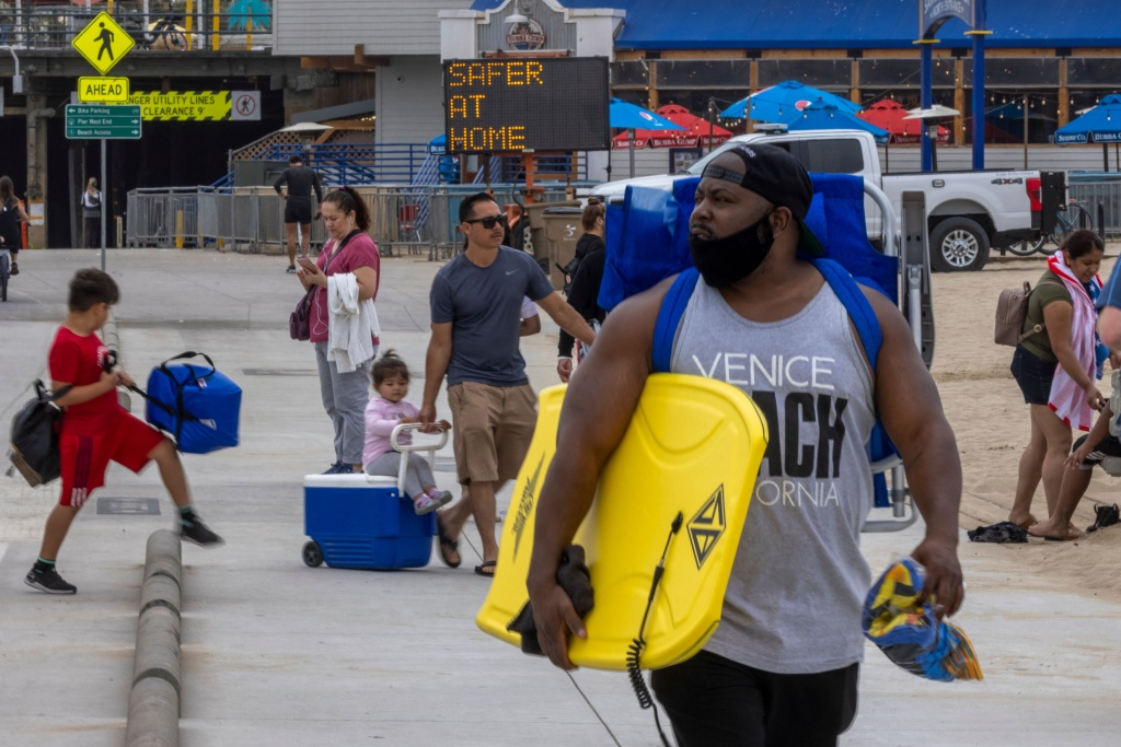 People walk near the Santa Monica Pier as crowds gather on Memorial Day as shutdowns are relaxed more than a year after Covid-19 pandemic shutdowns began, in Santa Monica, California on May 31, 2021.