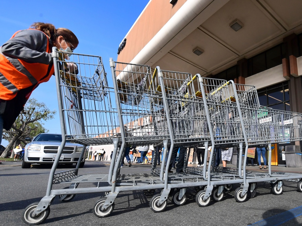 An employee pushes carts in Long Beach, Calif., at a Kroger store. The supermarket chain announced a $100 incentive bonus Friday for employees who  receive a COVID-19 vaccine.