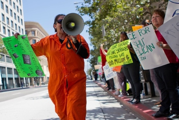A woman in prison garb leads protesters in chants of solidarity with prisoners on a hunger strike outside a state government building in Downtown Los Angeles on Monday morning.