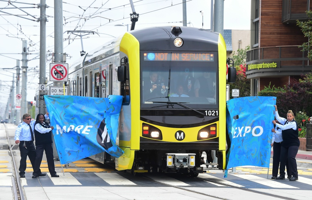 FILE: Los Angeles County Metropolitan Transportation Authority (Metro) employees hold up a banner for the first Expo Line train to Santa Monica on May 20, 2016. Measure M would continue Metro's rail building boom with $120 billion in projects over 40 years.
