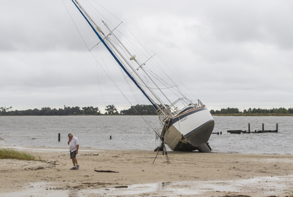 A large sailboat is washed ashore on a Biloxi, Mississippi beach by Hurricane Nate on Sunday, October 8, 2017.