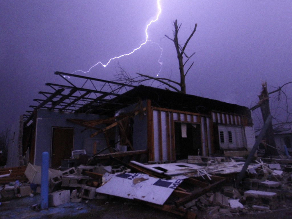 Lightning illuminates a house after a possible tornado touched down in Jefferson County, Ala., damaging several houses on Friday in Birmingham, Alabama.