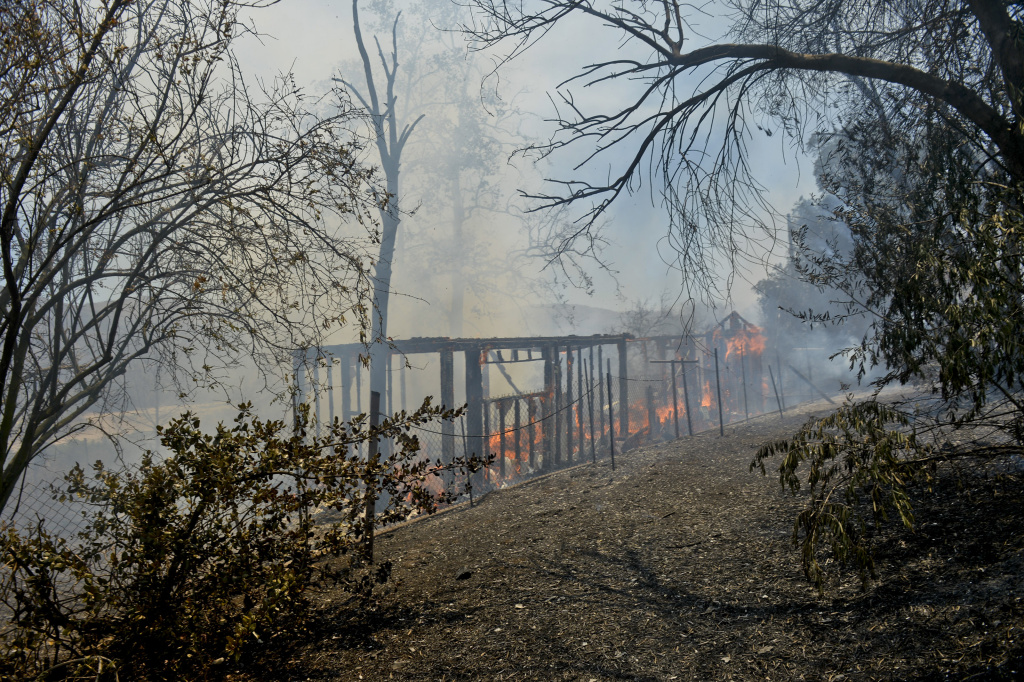 In file photo, an abandoned structure burns above Irvine Lake.