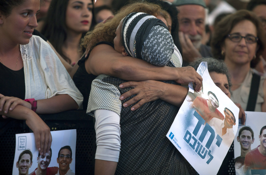 An Israeli woman hugs Iris Yifrah (from the back), mother of kidnapped Israeli teenager Eyal Yifrah During a rally under the slogan 'Bring Our Boys Home' on June 29, 2014 in Tel Aviv, Israel.Thousands of people gathered in Tel Aviv's Rabin Square on Sunday evening for a rally calling for the release of the three Israeli teens who were kidnapped more than two weeks ago.