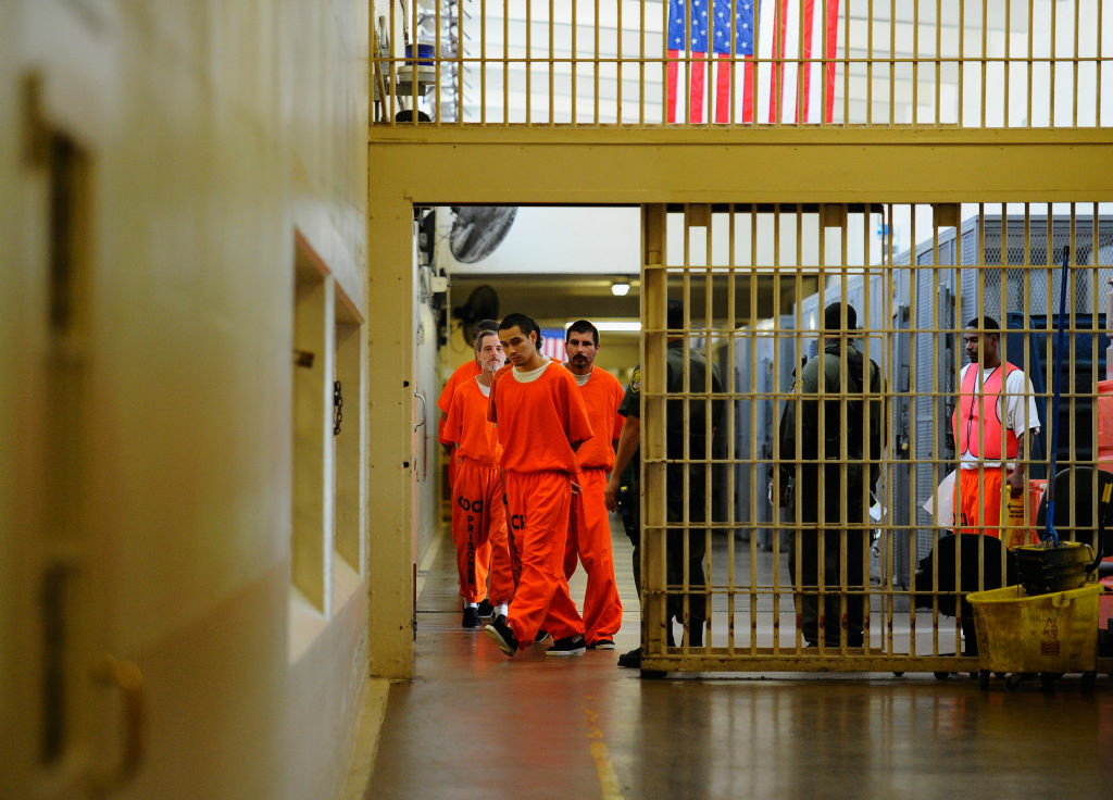 Inmates at Chino State Prison in Chino, CA walk the hallway.
