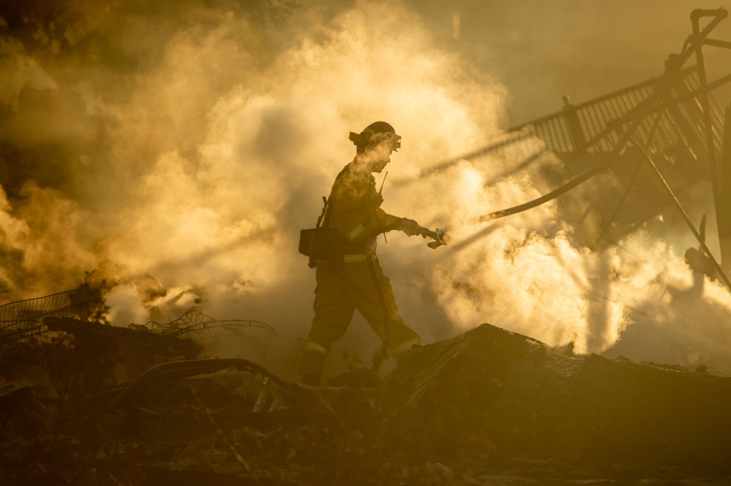 A firefighter sprays down the smoldering remains of a burning home during the Hillside Fire in the North Park neighborhood of San Bernardino, California on October 31, 2019.