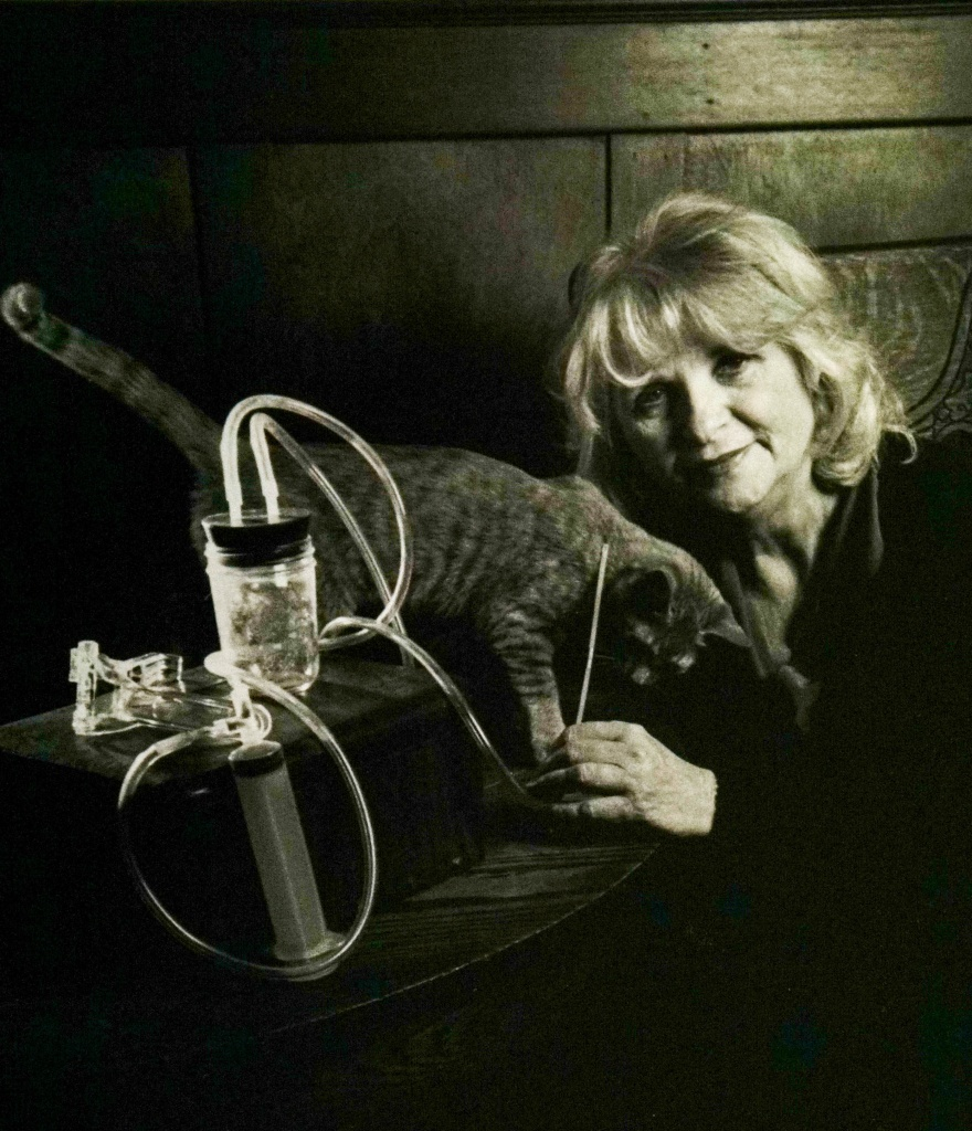 Carol Downer holding a Del-Em Kit, with her cat, Red