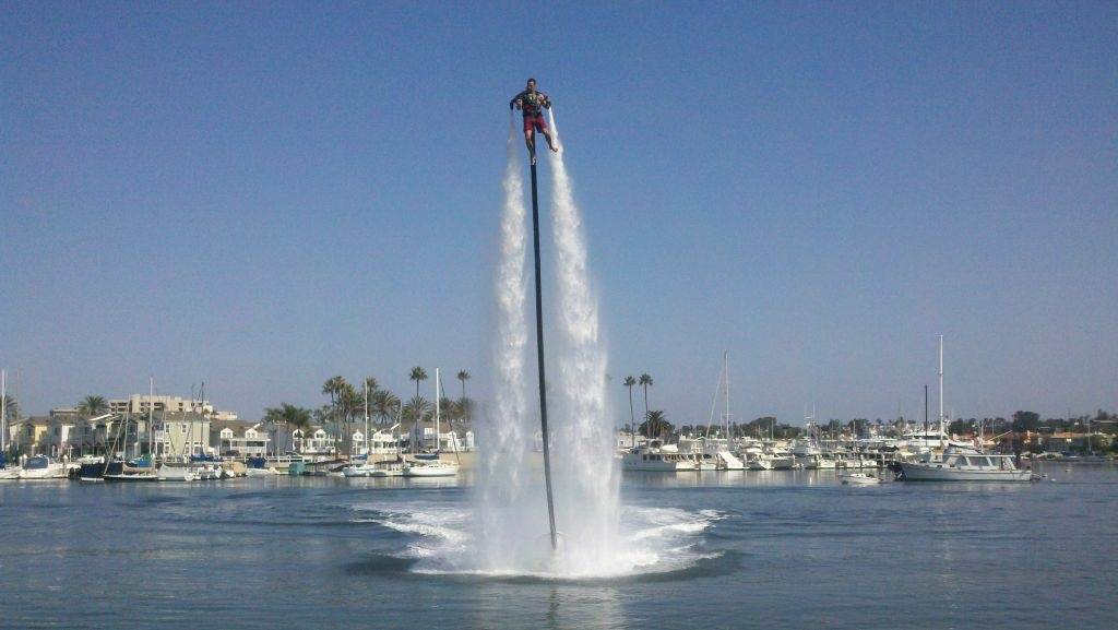 Adventurer Dean O'Malley blasts his way across Newport Harbor with a Jet Lev strapped to his back. O'Malley wants to use the water-powered jet pack to fly from Newport Beach to Catalina Island on Saturday.