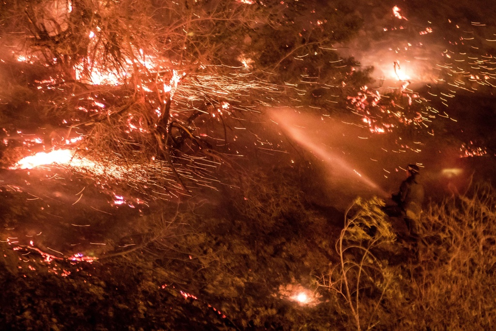 A man firefighter works to extinguish the Creek Fire as it burns along a hillside near homes and horses in the Shadow Hills neighborhood of Los Angeles, California, on December 5, 2017.