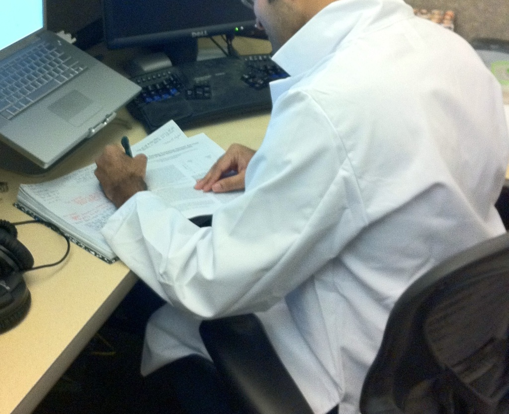 File: A researcher at CS/ECE wears a lab coat.
