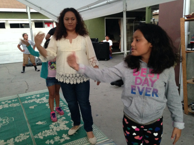 Sina Fifita instructs girls from her Tongan Methodist church in Lennox in a traditional Polynesian dance, to perform at a church service. Fifita, who lives in Hawthorne, said several peers have moved inland recently, including her best friend from high school.