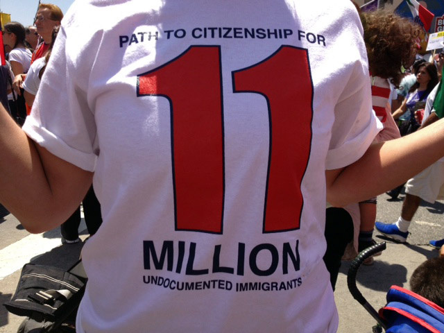 "A May Day protester at a Los Angeles immigration rally wears a ""Path to citizenship for 11 million undocumented immigrations"" t-shirt, May 1, 2013."