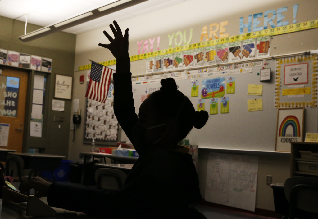 A first grade student raises her hand at Mary L. Fonseca Elementary School in Fall River, Mass., in November.