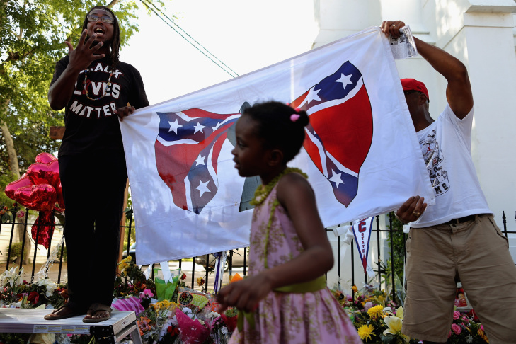 A young girl shouts slogans as hundreds of people gather for a protest rally against the Confederate flag in Columbia, South Carolina on June 20, 2015. The racially divisive Confederate battle flag flew at full-mast despite others flying at half-staff in South Carolina after the killing of nine black people in an historic African-American church in Charleston on June 17. On Monday, June 22, 2015, South Carolina Gov. Nikki Haley said the Confederate flag should be removed from the grounds of the state capitol, reversing her position on the divisive symbol amid growing calls for it to be removed.