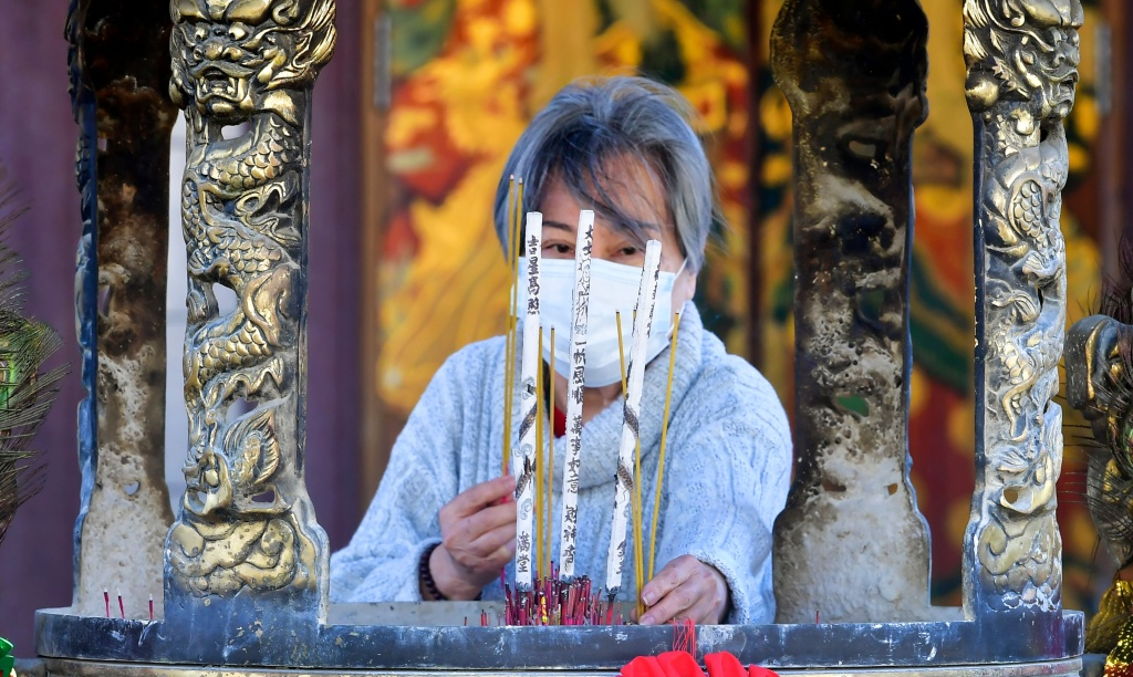 Incense is burned to mark the first day of the Lunar New Year of the Ox at the Thien Hau Temple, temporarily closed due to the coronavirus pandemic, in the Chinatown neighborhood of Los Angeles, California on February 12, 2021.