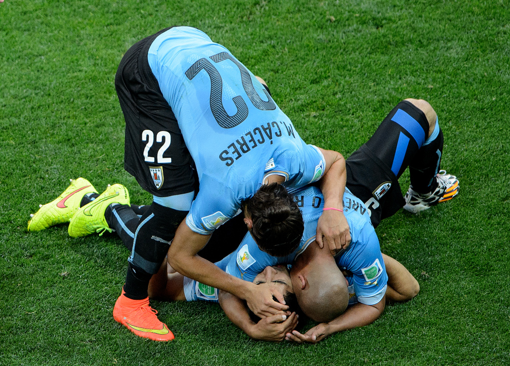 Luis Suarez of Uruguay falls onto the grass first to celebrate with teammates after scoring his team's first goal during the 2014 FIFA World Cup Brazil Group D match between Uruguay and England at Arena de Sao Paulo on June 19, 2014 in Sao Paulo, Brazil.