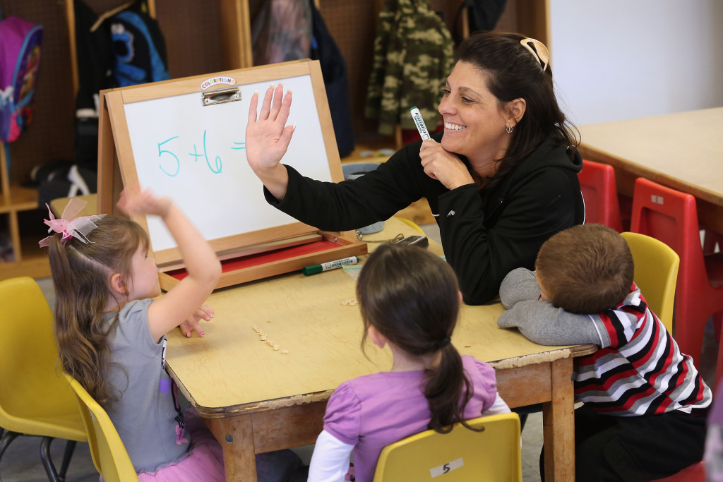 Teacher Denise Severing congratulates a child during a math lesson at the federally-funded Head Start school on September 20, 2012 in Woodbourne, New York. A California judge has struck down  teacher tenure protection, seniority-based job protection and existing disciplinary policy in a groundbreaking case for education equality.