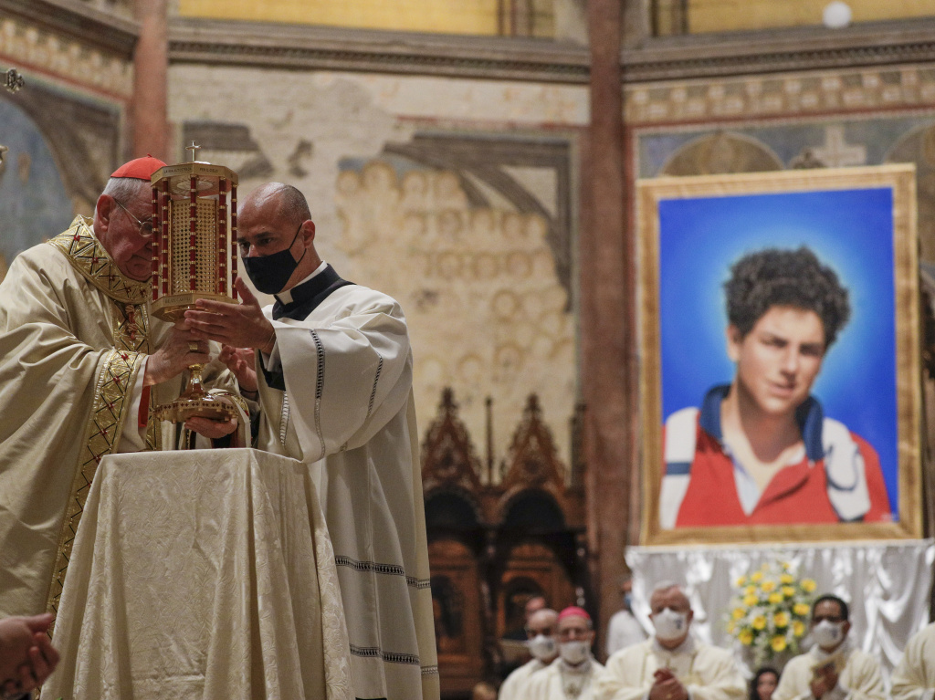 Cardinal Agostino Vallini, left, holds a relic of 15-year-old Carlo Acutis, an Italian boy who died in 2006 of leukemia, during his beatification ceremony celebrated in the St. Francis Basilica, in Assisi, Italy, on Saturday.