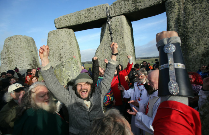 AMESBURY, ENGLAND - DECEMBER 21:  A man gestures as he watches the sun rise, as druids, pagans and revellers take part in a winter solstice ceremony at Stonehenge on December 21, 2012 in Wiltshire, England. Predictions that the world will end today as it marks the end of a 5,125-year-long cycle in the ancient Maya calendar, encouraged a larger than normal crowd to gather at the famous historic stone circle to celebrate the sunrise closest to the Winter Solstice, the shortest day of the year.  (Photo by Matt Cardy/Getty Images)