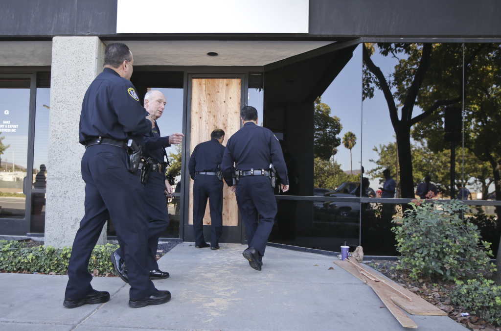San Diego Police Chief William Lansdowne, second from left, and other law enforcement officials approach the door of an office in Otay Mesa area of San Diego.