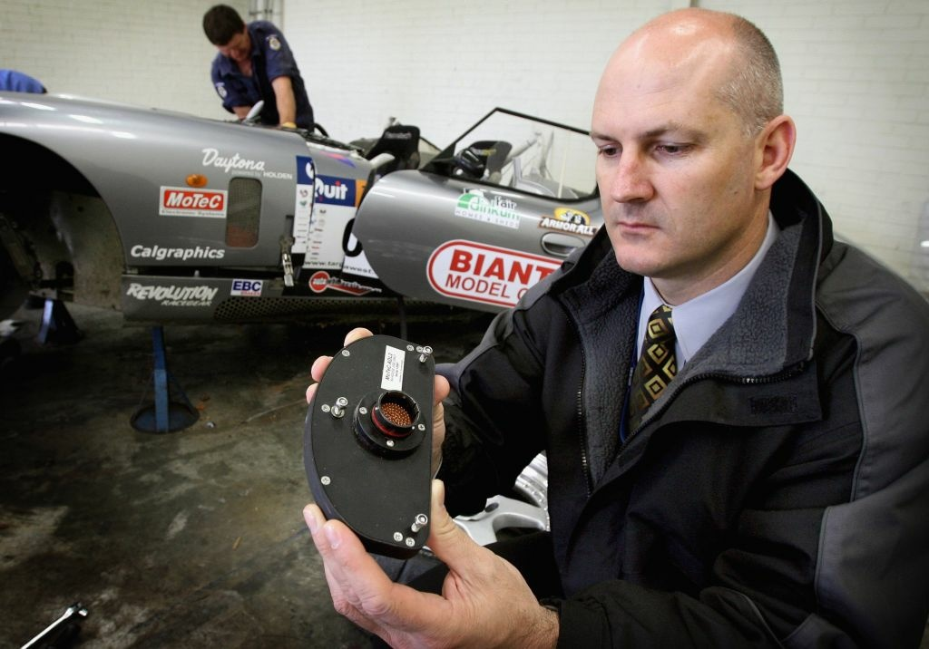 Major crash investigation section officer inspects the 'black box' recorder that was recovered from a car crash in Australia. Should black boxes be implemented in the U.S.?