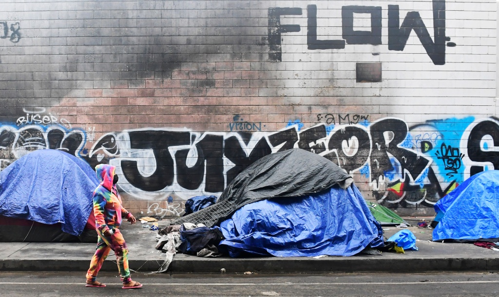 A woman walks past tents for the homeless lining a street in Los Angeles, California on February 1, 2021.