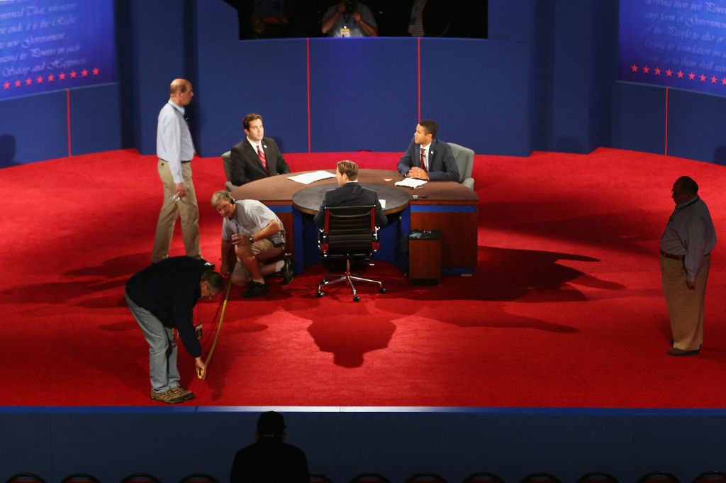 Stand-ins for Republican presidential candidate Mitt Romney, moderator Bob Scheiffer, and U.S. President Barack Obama seated at the debate table participate in a stage rehearsal as workers continue to prepare the stage for the final presidential debate Monday night at Lynn University in Boca Raton, Florida. From left to right are Lynn University students A.J. Mercincavage, Andrew Lippi, and Eric Gooden.