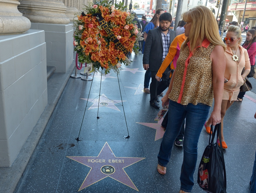 People walk past flowers placed before the Star for Roger Ebert on Hollywood's Walk of Fame April 4, 2013 in Hollywood,California. Ebert, the first film critic to win a Pulitzer Prize, died April 4, 2013, the US newspaper that employed him for more than four decades said. He was 70. Ebert -- who just two days ago announced in a blog post that he was taking a break from his main job -- succumbed to cancer after a long battle, according to the Chicago Sun-Times.