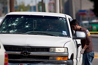 A member of the Mexican police looks into a pick up truck in Ciudad Juarez, on March 25, 2010, where two corpses were found.