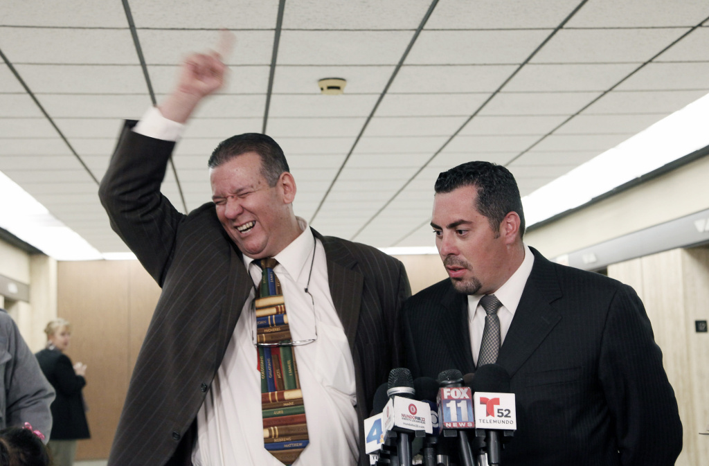 Former Councilman Luis Artiga, left, celebrates his acquittal, standing with his attorney George Mgdesyan during a news conference after the Bell trial verdicts were read Wednesday March 20, 2013 in Los Angeles. Five former elected officials of the tiny California city of Bell were convicted Wednesday of multiple counts of misappropriation of public funds, and a sixth defendant, Artiga, was cleared entirely.