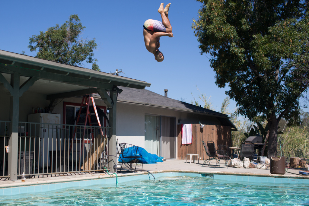 Robert Woodley jumps into a pool at his home in Highland Park.