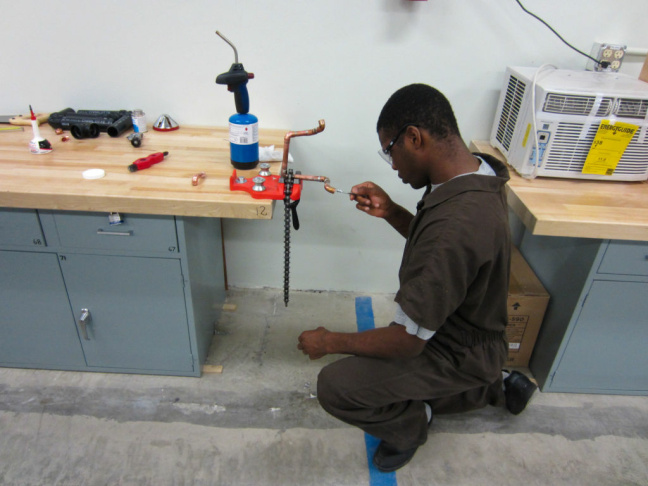 Keimond, 18, expertly measures out pieces of wood, marking them with a pencil. He is working on making a cabinet and had already finished some bookshelves in the camp's brand new building skills program. The shop rivals any high-tech woodshop outside the camp's walls, except that the equipment is attached to the tables.