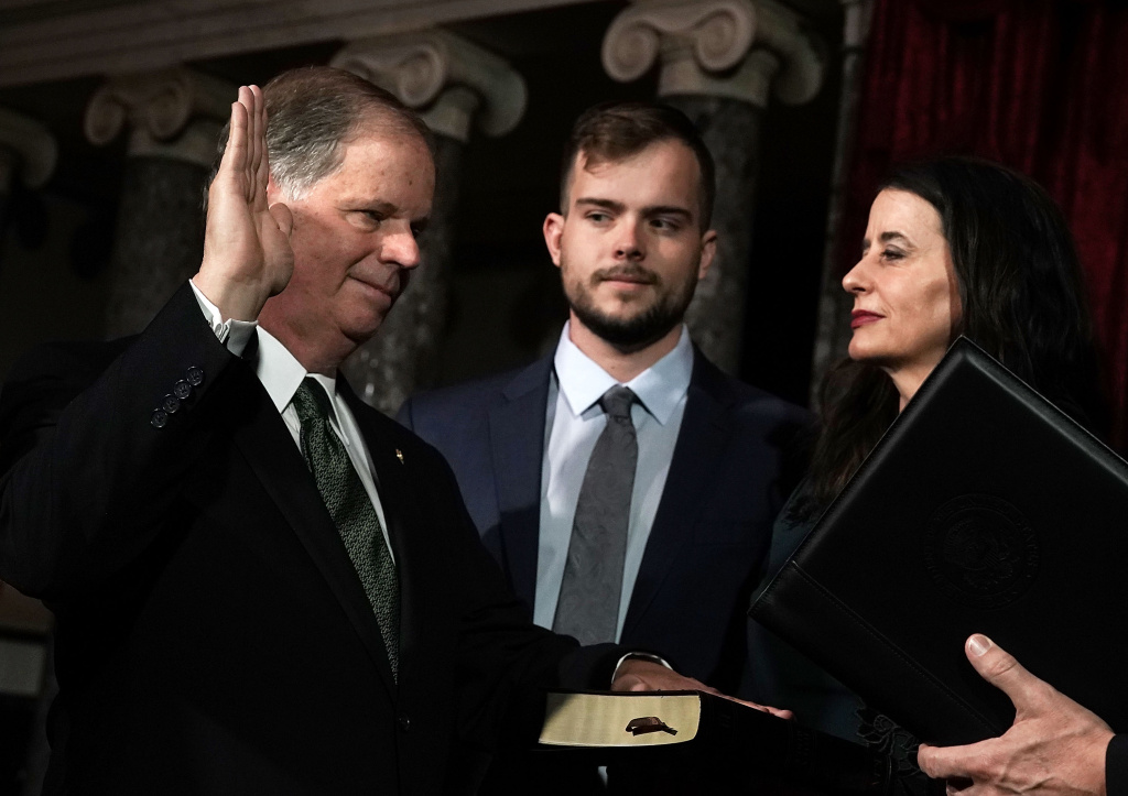U.S. Sen. Doug Jones (D-AL) (L) participates in a mock swearing-in ceremony as Jones' wife Louise (R) and son Carson (2nd L) look on at the Old Senate Chamber of the U.S. Capitol January 3, 2018 in Washington, DC.