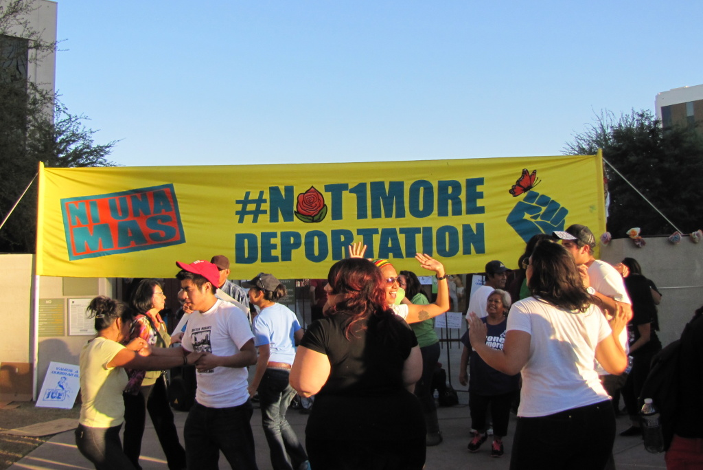 Demonstrators danced into the late afternoon in front of the ICE office in Phoenix under a banner they hung themselves on the front gate.