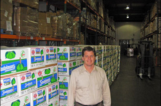 Michael Flood, executive director of the L.A. County Regional Food Bank, next to pears that will feed the hungry. When the U.S. government cut back on the food it gave out, the Food Bank made up the gap with fresh produce.