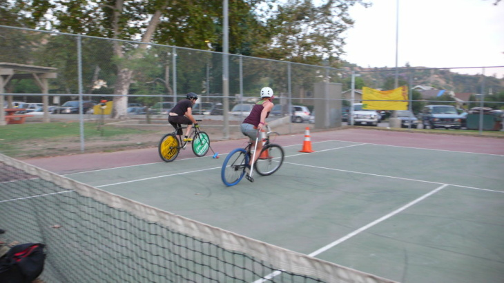 Bike polo players tripod using their mallets in order to stay upright.