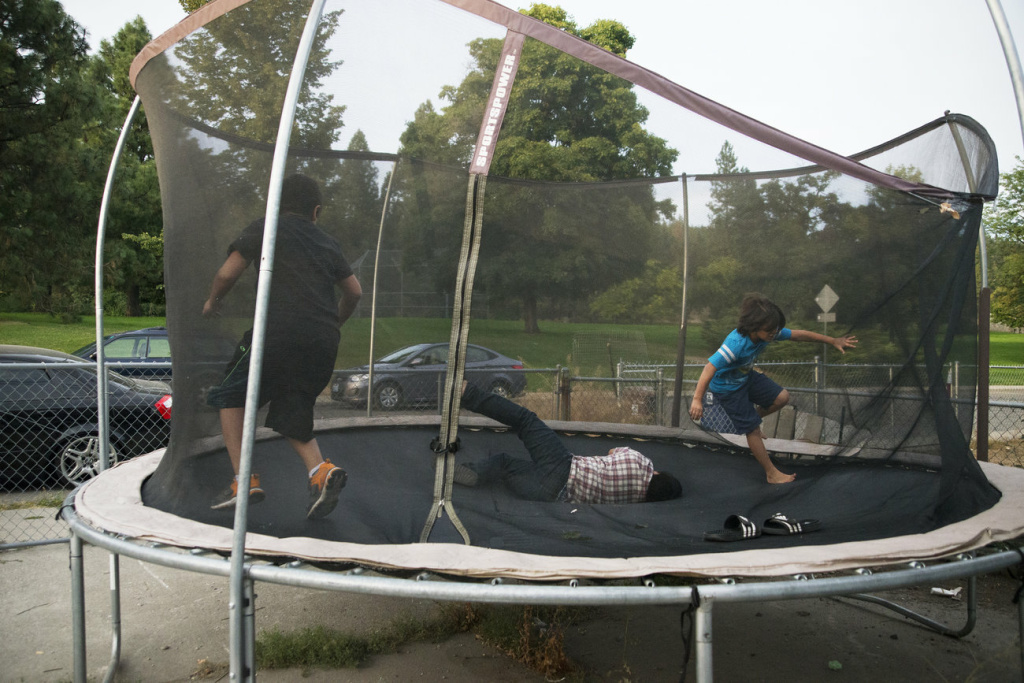 Three of Manuel and V's sons play on the trampoline in their backyard. Manuel was away from his family for six months.