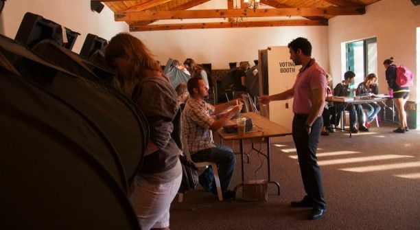 Allan Hull, clerk, gives Vladimir  Gulkarov his code to vote at the George G. Golleher Alumni House during the 2012 presidential elections at Cal State University, Fullerton in Fullerton, Calif., Tuesday, November 6, 2012. Local residents were given a chance to vote at the polling location at the university campus.
