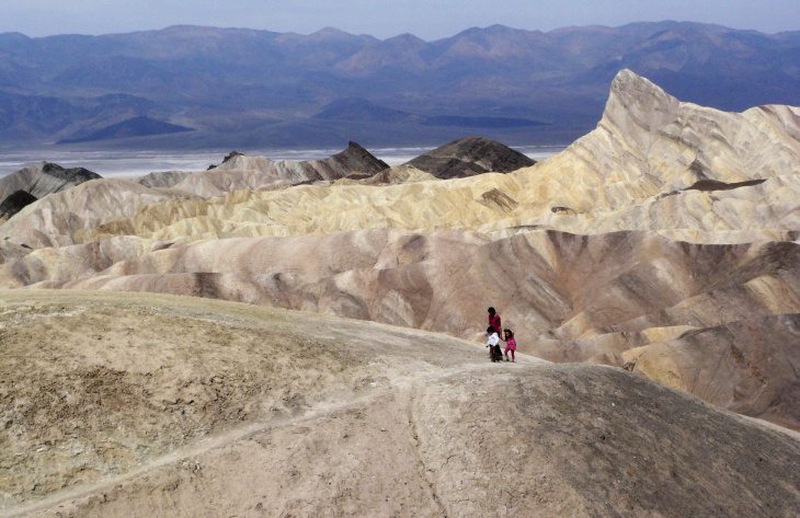 In this April 11,2010 file photo, tourists walk along a ridge at Death Valley National Park, Calif. Death Valley National Park is expected to reach its first 120-degree day of the year on Sunday, June 18, 2017, and temperatures could creep toward 124 by Tuesday as the sweltering system envelopes much of the region.