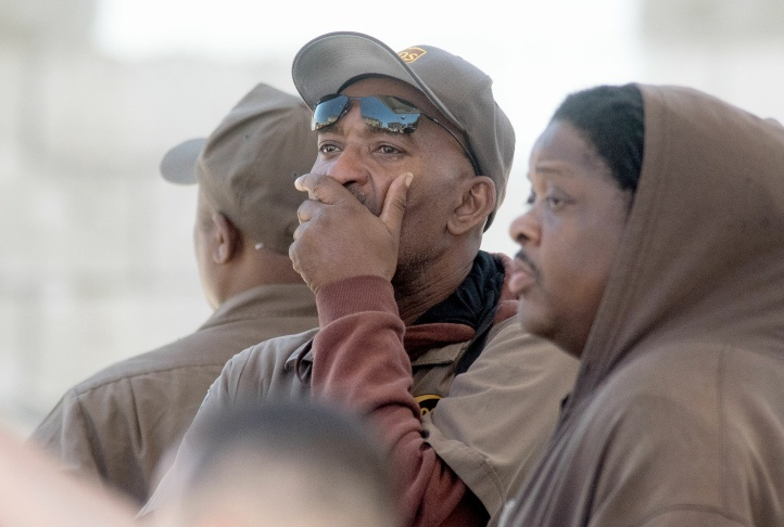 UPS workers gather outside a UPS package delivery warehouse where a shooting took place Wednesday, June 14, 2017, in San Francisco. A UPS spokesman says four people were injured in the shooting at the facility and that the shooter was an employee..