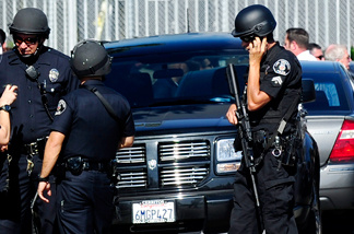 Police and sherriffs deputies maintain a command post outside Gardena High School in Los Angeles January 18, 2010 where two students suffered gunshot wounds after a pistol in a 10th-grader's backpack accidentally discharged when he dropped the bag.
