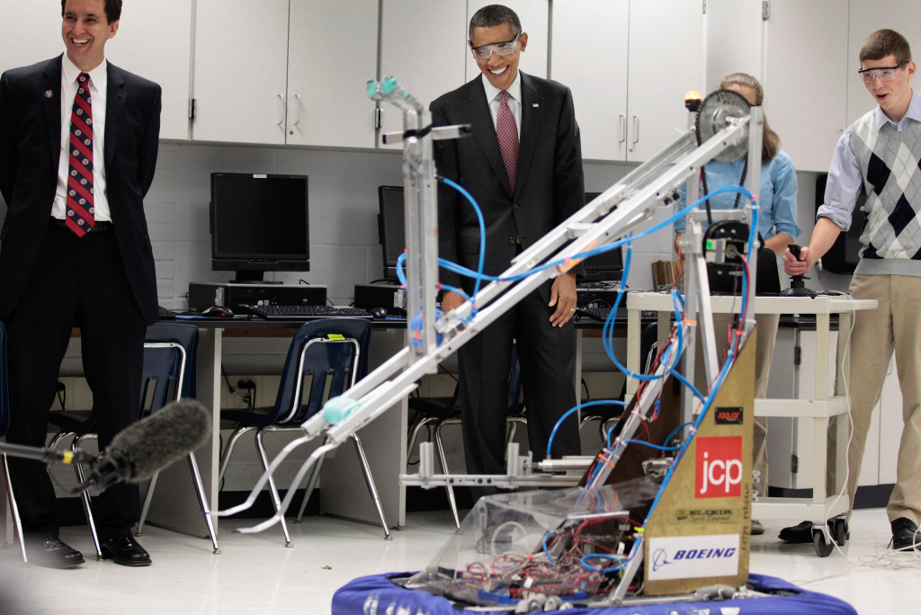 U.S. President Barack Obama visits a classroom and watches students Meghan Clark and Nathan Hughes (R) demonstrate the FIRST Robot, a robot created in the school's prototyping and robotics senior research labs for last year's FIRST Robotics Competition, at Thomas Jefferson High School for Science and Technology September 16, 2011 in Alexandria, Virginia. Later in the morning Obama signed the America Invents Act, which reforms patent law so to give a patent to the first applicant rather than the first inventor and allows the woefully underfunded U.S. Patent and Trade Office to set and potentially keep its own fees.