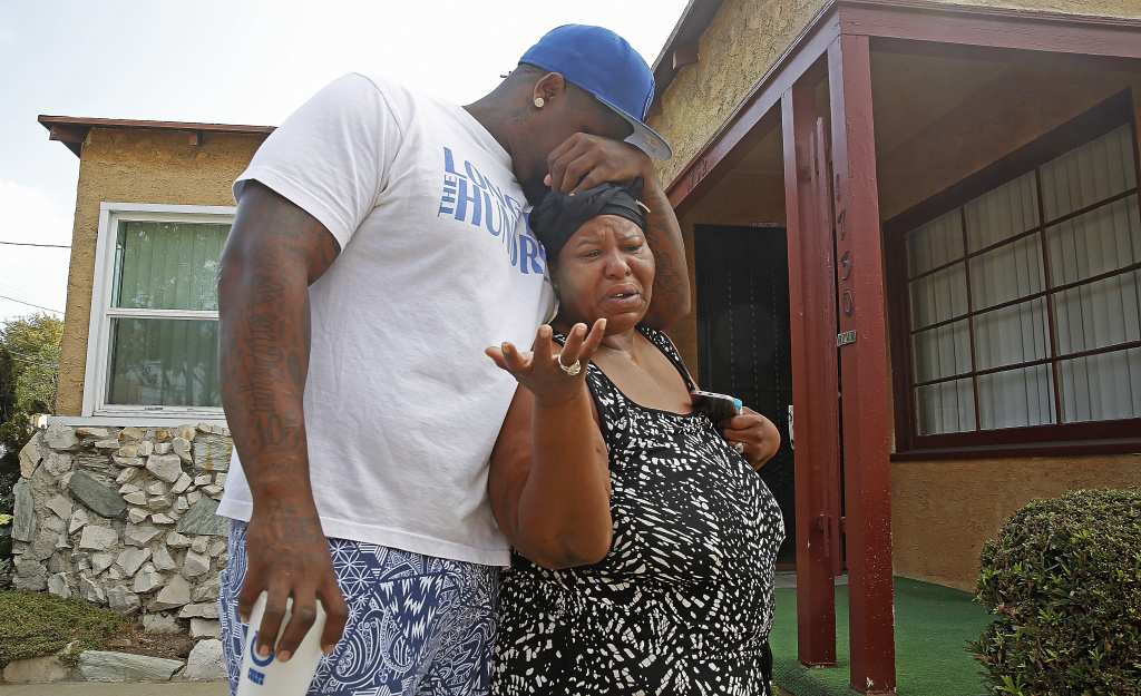 A neighbor embraces an unidentified woman by a driveway of a home where Los Angeles Police officers shot and killed Carnell Snell Jr. in Los Angeles on Sunday, Oct. 2, 2016. Snell was killed in south Los Angeles on Saturday at the end of a car chase, sparking a protest by several dozen people angered by another fatal police shooting of a black man.