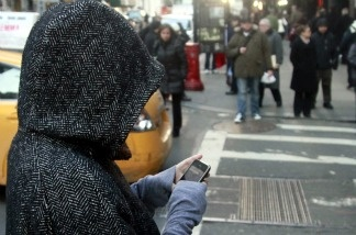 A pedestrian uses a phone by a crosswalk in New York City.